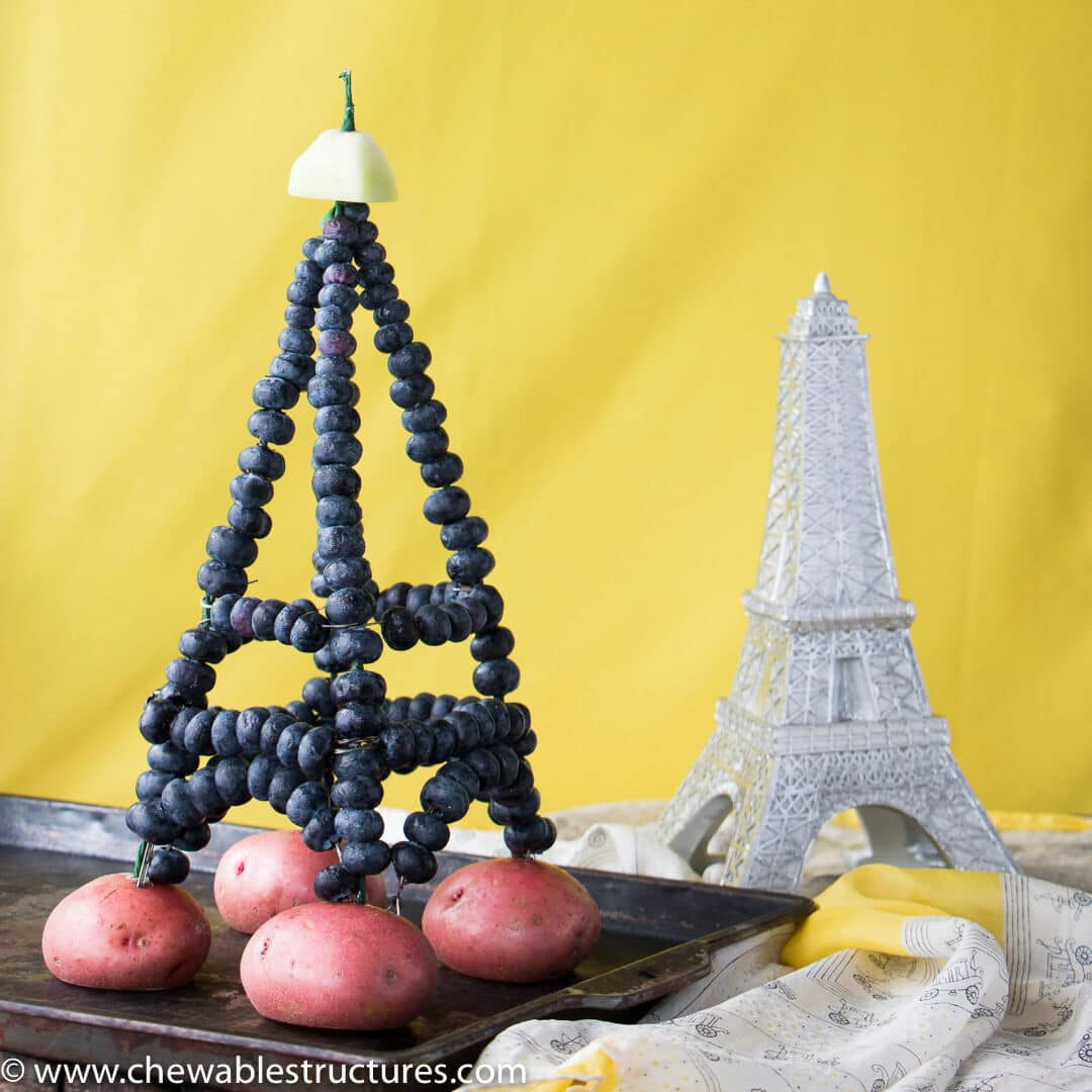 Eiffel tower made of wires strung through fresh blueberries and topped with a honeydew deck.