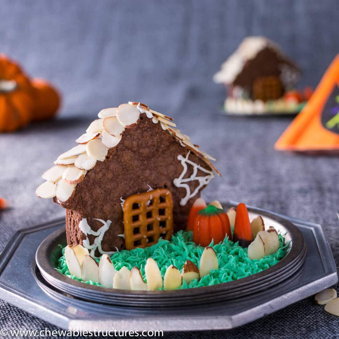 House-shaped chocolate brownie topped with shaved almond roof shingles and fence. The house is deocrated with candy corn, a pretzel door and green icing grass.