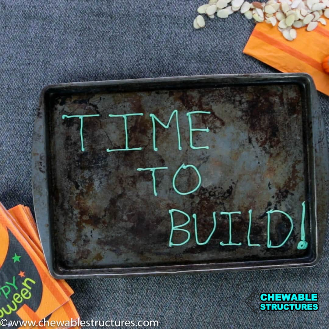 "The words ""Time to Build"" is written in icing on a cookie sheet."