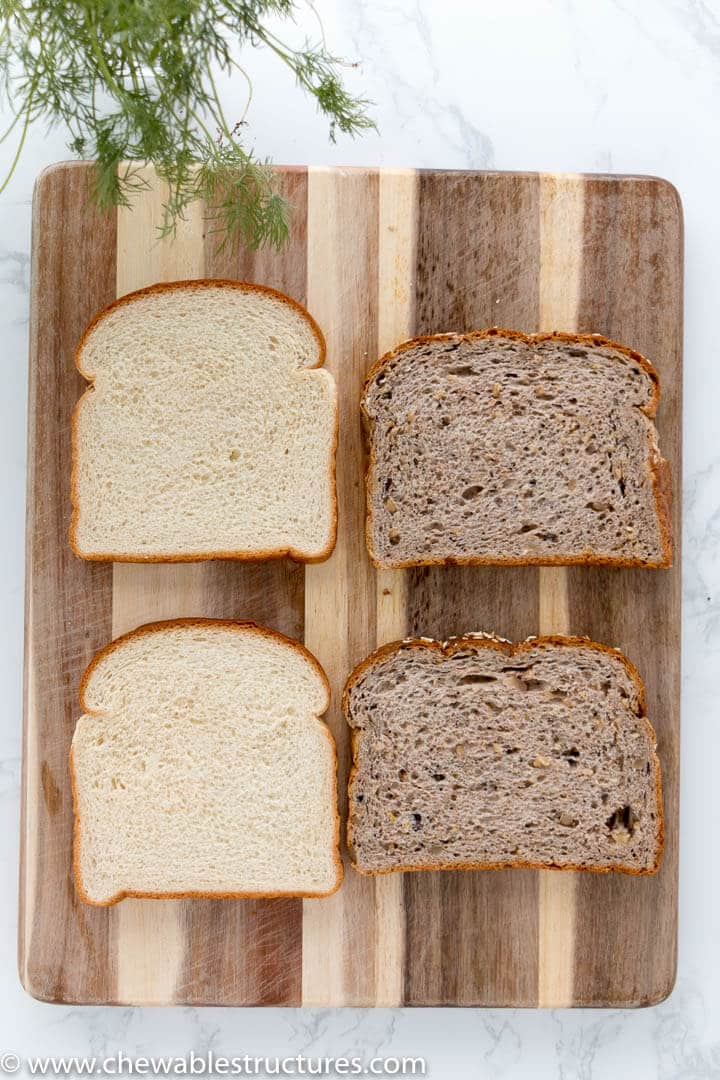 Top view of fresh white bread and whole wheat bread on a cutting board. Bread is used to make cucumber sandwiches.