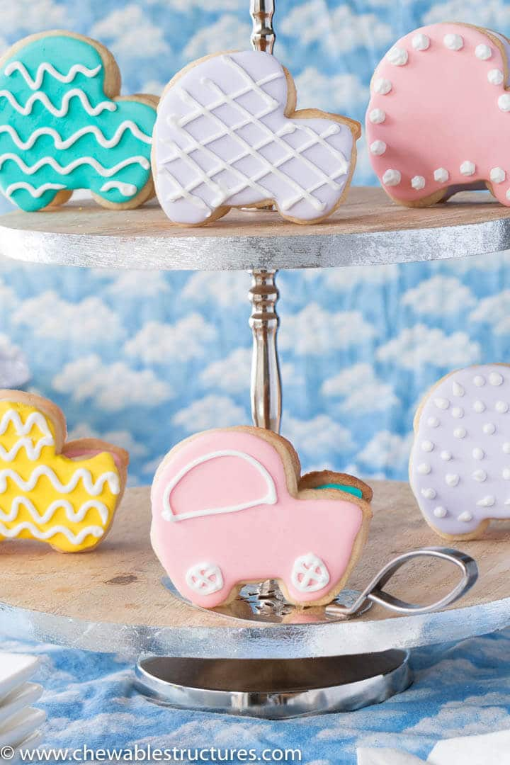 baby shower cookies shaped like baby carriages displayed on a two tier serving tray.