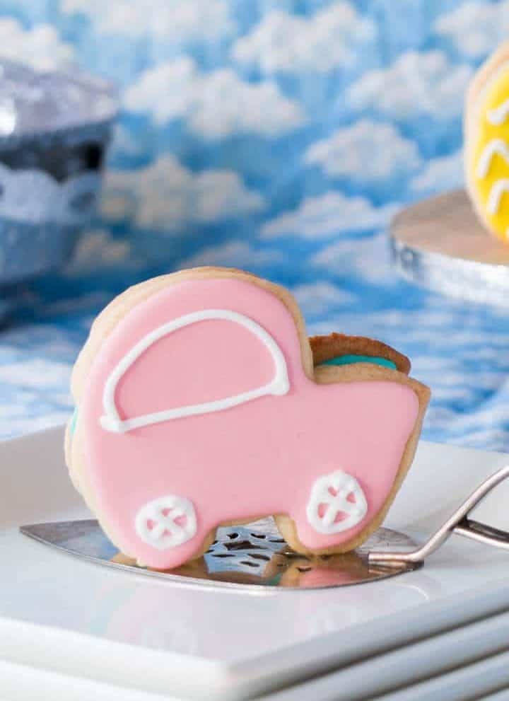 Baby shower cookies shaped like baby carriages standing vertically on a serving plate. Cookies are made of Betty Crocker Sugar Cookie Mix.