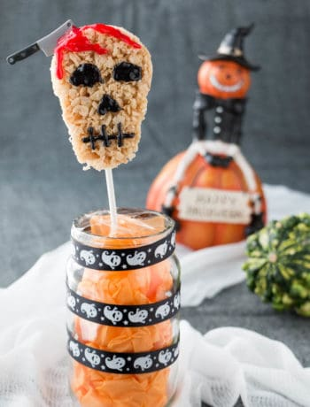 Skull-shaped Halloween Rice Krispie Treats standing vertically on a treat stick.