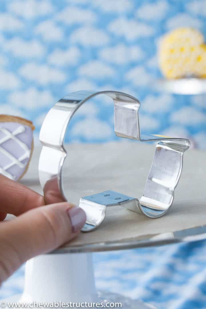 A hand hold a cookie cutter shaped like a baby carriage, which is used to make cut out sugar cookies.