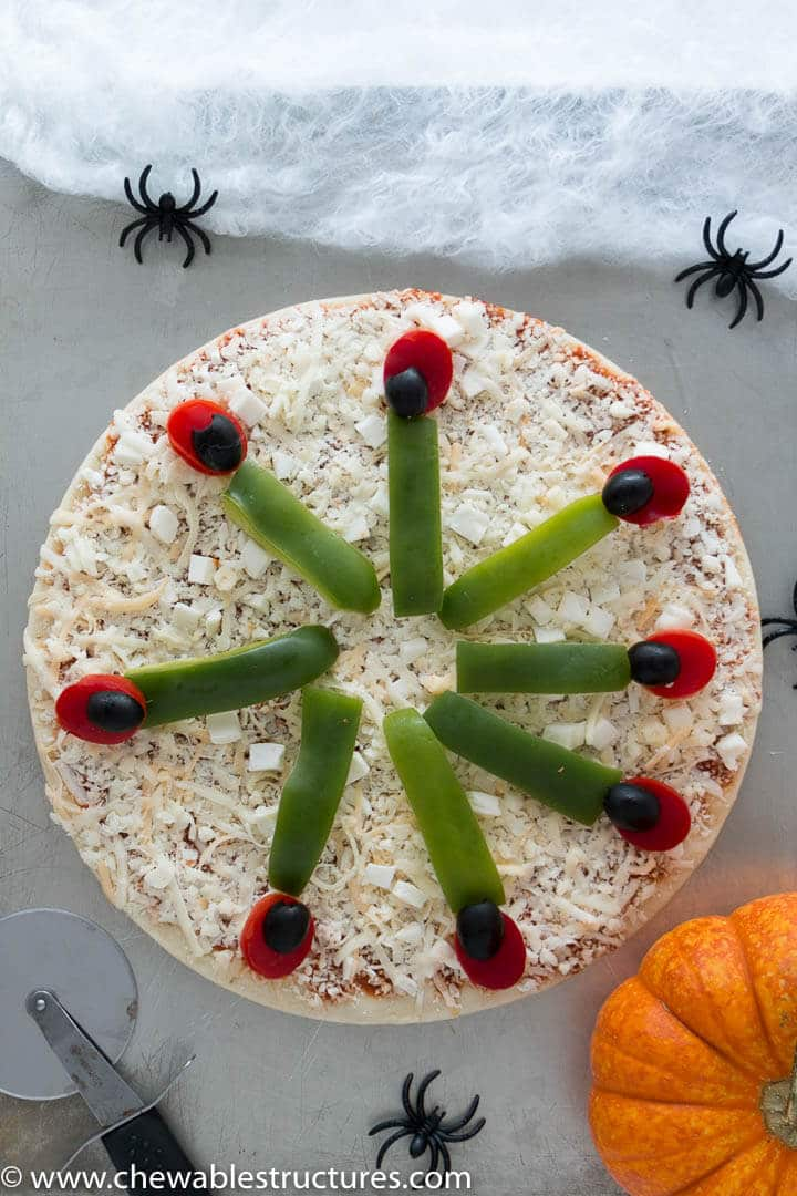 Uncooked whole Halloween pizza on a baking sheet.