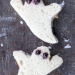 ghost-shaped peanut butter and jelly sandwiches on a cookie sheet