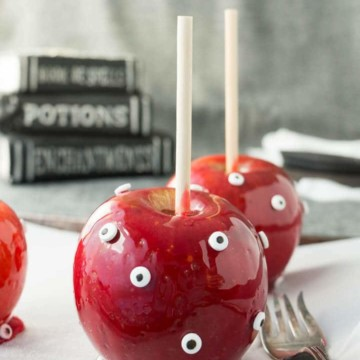 A candy apple covered with candy eyeballs.