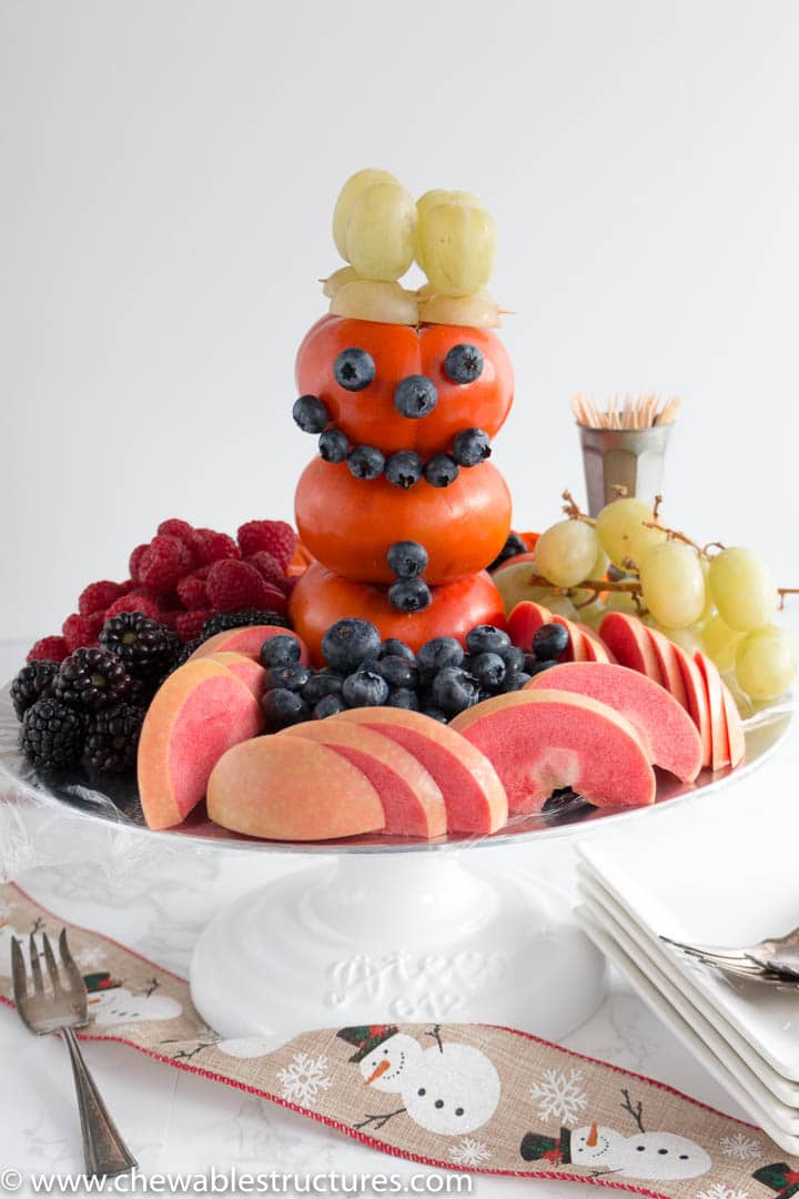 An edible 3-D snowman made of Fuyu persimmon, blueberries, and green grapes.