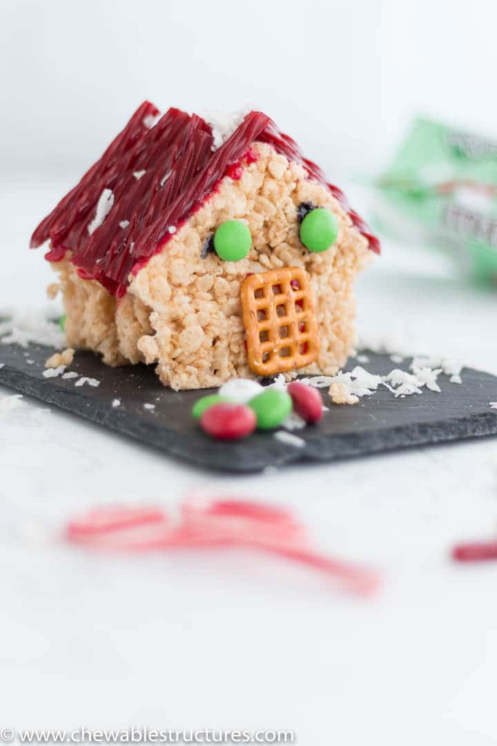 edible 3D house made of christmas rice krispie treats, red licorice roof shingles, mint M&M windows, pretzel doorway, and coconut snowflakes.