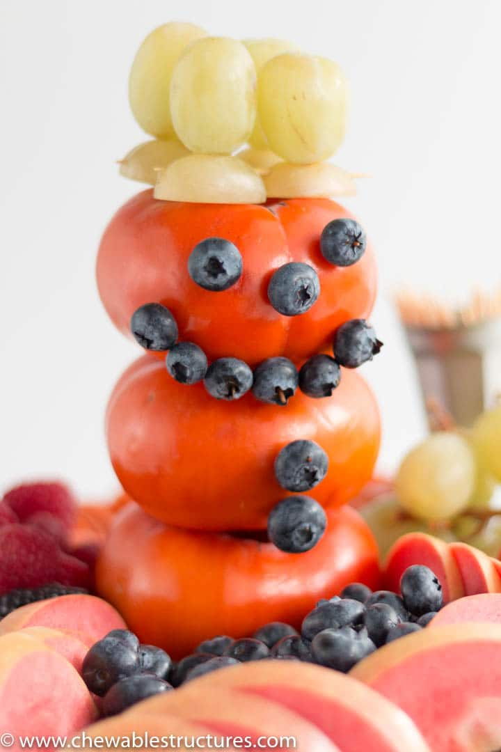 A baby shower fruit tray featuring an edible 3-D snowman made of Fuyu persimmon, blueberries, and green grapes.