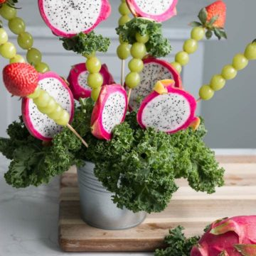 dragon fruit bouquet made of dragon fruit, green grapes, and strawberries on a table